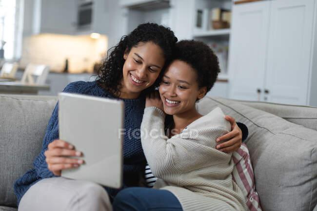 Змішана расова лесбійська пара сидить на дивані за допомогою цифрового планшету. Якість самоізоляції вдома під час коронавірусу covid 19 пандемії. — стокове фото