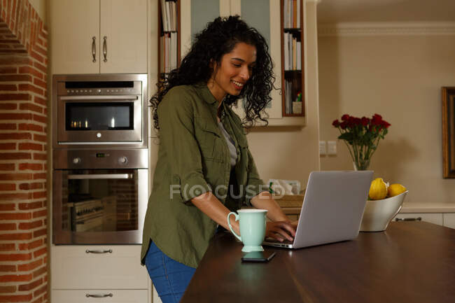 Mixed race woman using laptop standing in kitchen. self isolation at home during covid 19 coronavirus pandemic. — Stock Photo
