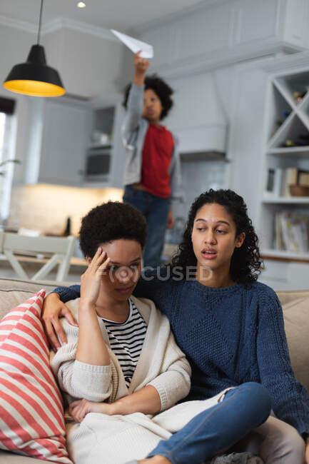 Lesbisches Paar mit gemischter Rasse, das auf der Couch sitzt und redet. Selbst-Isolation Qualität Familienzeit zu Hause zusammen während Coronavirus covid 19 Pandemie. — Stockfoto