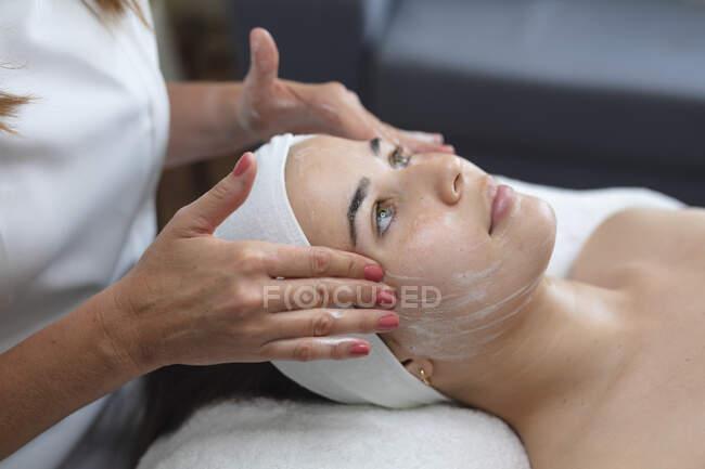 Mujer caucásica tumbada mientras esteticista le da un facial. cliente disfrutando del tratamiento en un salón de belleza. - foto de stock