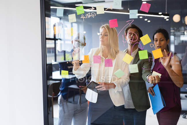 Diverse business people brainstorming by glass board in office. modern creative business professionals meeting workplace. — Stock Photo