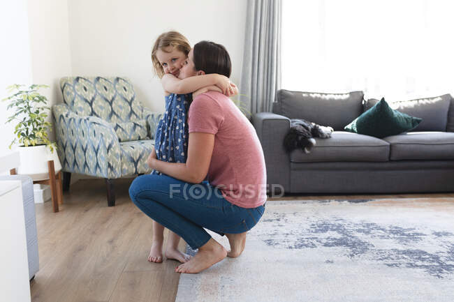 Caucasian mother and daughter having fun hugging and kissing in living room. enjoying quality time at home during coronavirus covid 19 pandemic lockdown. — Stock Photo