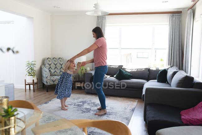 Кавказька мати і дочка добре танцюють у вітальні. Якісний час, проведений під час коронавірусного ув