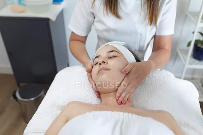 Кавказька жінка лягла спиною, а косметолог дав їй обличчя. Клієнт отримує задоволення від лікування в салоні краси.. — стокове фото