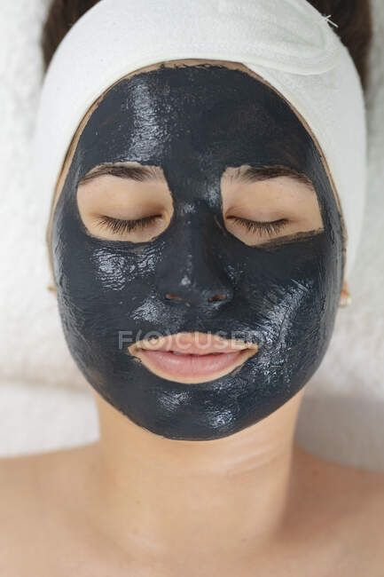 Caucasian woman lying back while beautician applies a face mask. customer enjoying treatment at a beauty salon. — Stock Photo