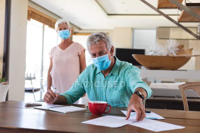 Casal caucasiano sénior a usar máscaras na cozinha. um homem sentado à mesa a pagar contas. em casa em auto-isolamento durante coronavírus covid 19 bloqueio pandêmico — Fotografia de Stock