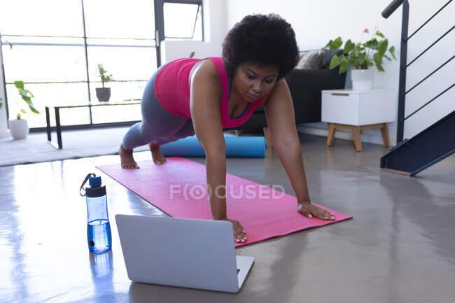 Африканская американка использует ноутбук, тренируясь в спортивной одежде. самоизоляция фитнес-технологии связи в домашних условиях во время коронавируса ковид 19 пандемии. — стоковое фото