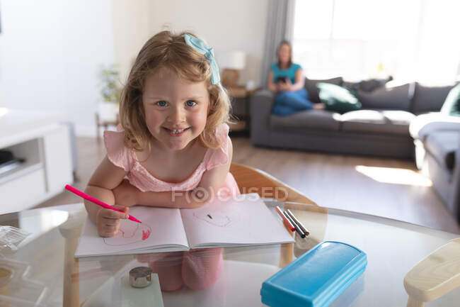 Smiling caucasian girl in living room, drawing in notebook. enjoying quality time at home during coronavirus covid 19 pandemic lockdown. — Stock Photo