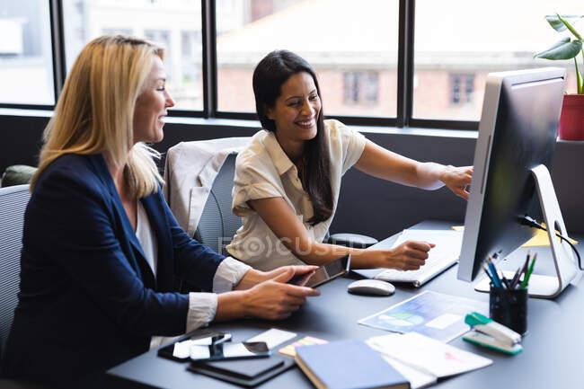 Різні бізнесмени, які сидять за столом, використовують комп'ютерні обговорення в офісі. Сучасний офісний бізнес, спільна робота з мозковим штурмом. — стокове фото