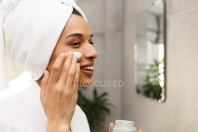 Smiling mixed race woman applying face cream in bathroom. self isolation at home during covid 19 coronavirus pandemic. — Stock Photo