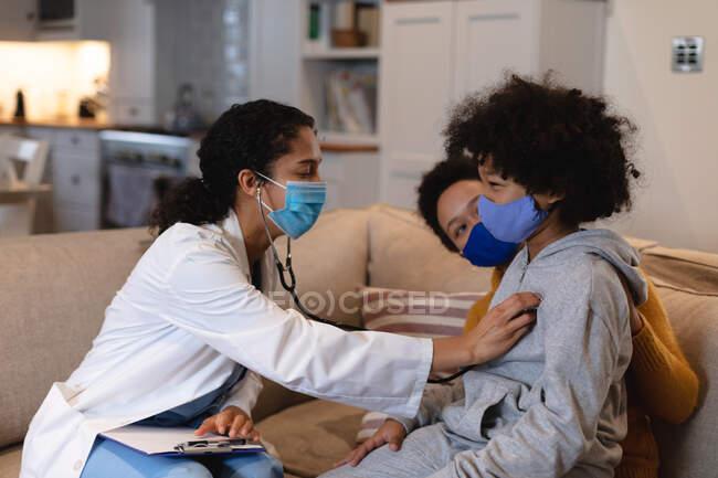 Menina de raça mista usando máscara facial sendo examinada por mestiça médica sentada no sofá. auto-isolamento em casa juntos durante coronavírus covid 19 pandemia. — Fotografia de Stock