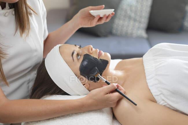 Donna caucasica sdraiata mentre estetista applica una maschera facciale. cliente che si gode il trattamento in un salone di bellezza. — Foto stock