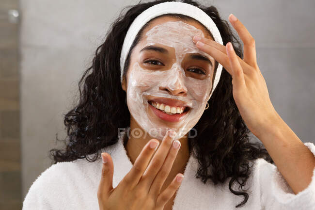 Portrait of mixed race woman applying face cream in bathroom. self isolation at home during covid 19 coronavirus pandemic. — Stock Photo