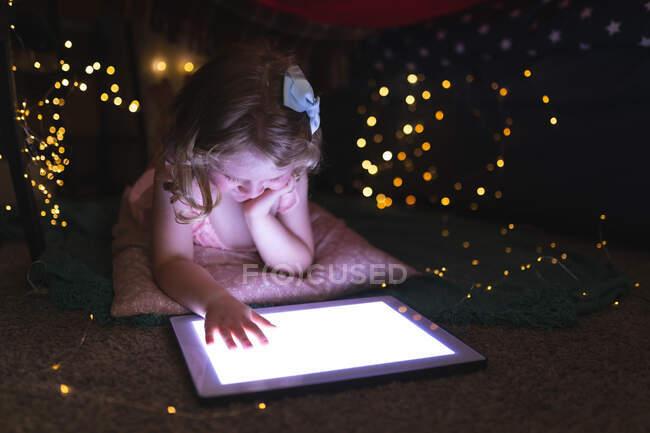 Fille caucasienne couchée dans la chambre à coucher en utilisant une tablette numérique le soir. profiter d'un temps de qualité à la maison pendant le confinement de coronavirus covid 19 pandémie. — Photo de stock