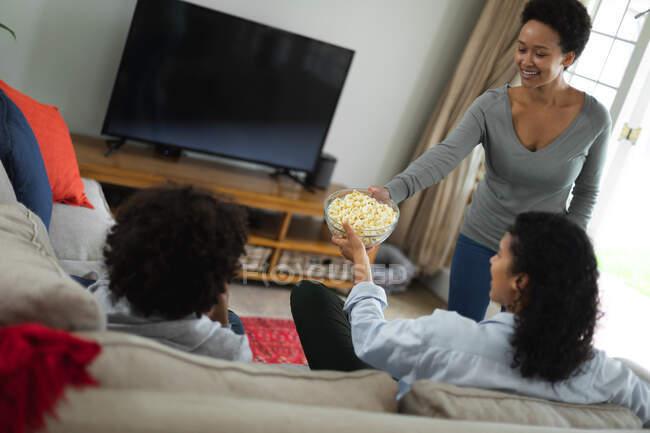 Misto razza lesbica coppia e figlia seduta sul divano a guardare la tv e mangiare popcorn. auto isolamento qualità famiglia tempo a casa insieme durante coronavirus covid 19 pandemia. — Foto stock