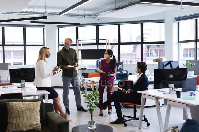 Различные бизнесмены, носящие маски для лица, штурмуют офис. защитное рабочее место в офисе во время пандемии коронавируса. — стоковое фото