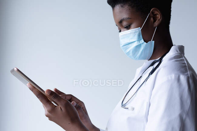 Mixed race female doctor wearing face mask standing and using digital tablet. medical professional healthcare worker hygiene during coronavirus covid 19 pandemic. — Stock Photo