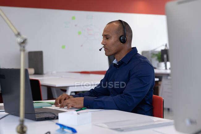 Mixed race businessman sitting wearing headphones using laptop in modern office. business modern office workplace technology. — Stock Photo