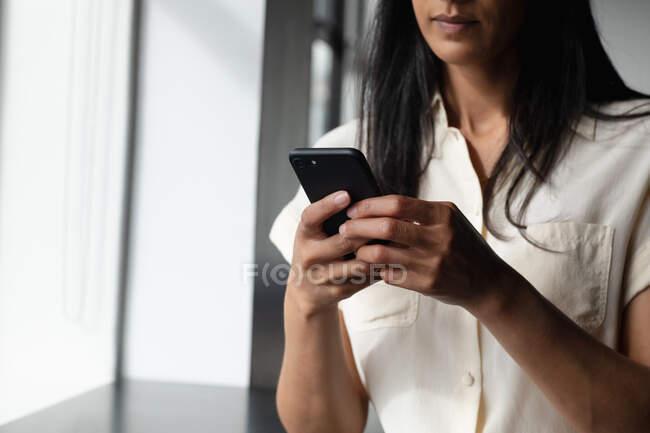 Деловая женщина смешанной расы, стоящая у окна со смартфоном в современном офисе. современная офисная технология. — стоковое фото