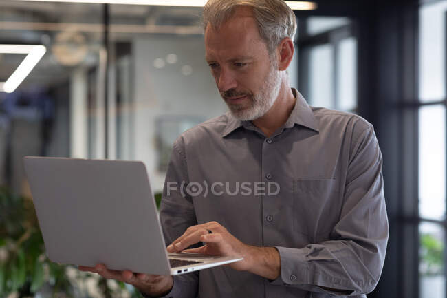 Caucasian businessman standing by window using laptop in modern office. business modern office workplace technology. — Stock Photo