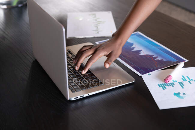 Бізнесмен стоїть за допомогою ноутбука, який проходить через паперову роботу в сучасному офісі. Технологія сучасного офісу. — стокове фото