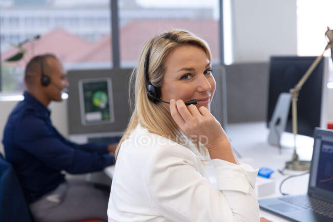 Caucasian businesswoman sitting wearing headphones looking at camera and smiling in modern office. business modern office workplace technology. — Stock Photo