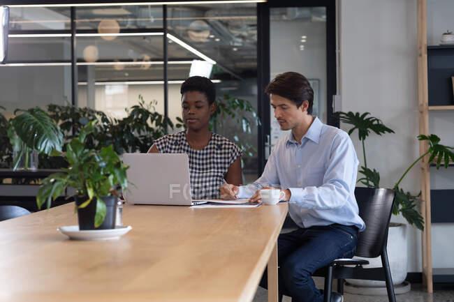 Різні ділові люди сидять за допомогою ноутбука, який проходить через паперову роботу в сучасному офісі. Технологія сучасного офісу. — стокове фото