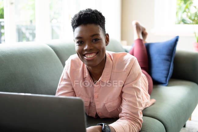 Портрет афро-американської жінки лежав на дивані, використовуючи ноутбук, який працював з дому. Дивиться на камеру і посміхається. Перебуваючи вдома в ізоляції під час карантину.. — стокове фото