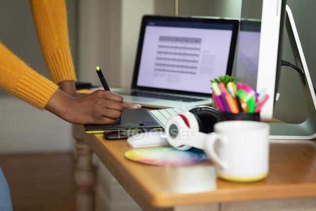 Seção média da mulher afro-americana usando tablet gráfico enquanto trabalhava em casa. ficar em casa em auto-isolamento em quarentena — Fotografia de Stock