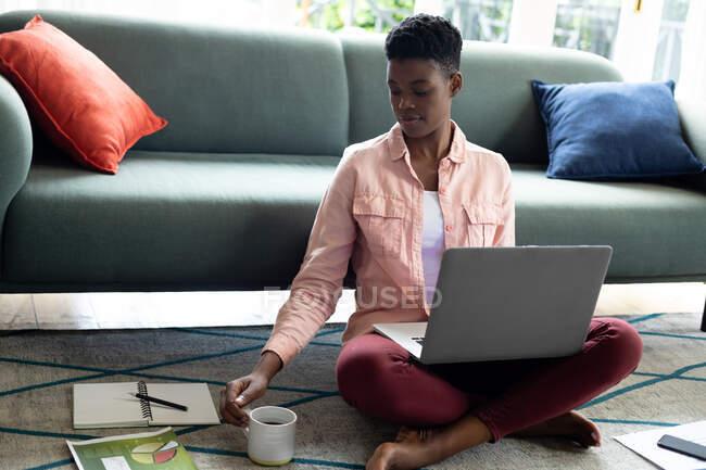 Donna afroamericana seduta sul pavimento che beve caffè da casa. stare a casa in isolamento durante l'isolamento in quarantena. — Foto stock