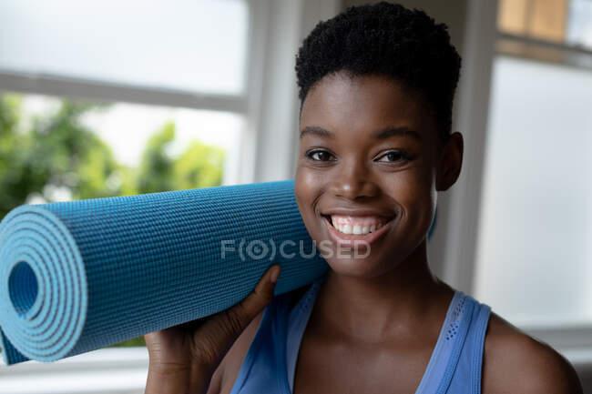 Портрет африканской американки, улыбающейся, держа дома коврик для йоги. оставаться дома в изоляции в карантинной изоляции — стоковое фото