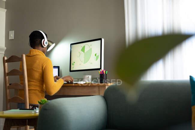 Afro-americana usando fones de ouvido usando computador enquanto trabalhava em casa. ficar em casa em auto-isolamento em quarentena — Fotografia de Stock