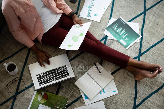 Mulher afro-americana sentada no chão usando laptop passando por papelada de casa. ficar em casa em auto-isolamento durante o confinamento de quarentena. — Fotografia de Stock