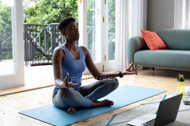 Африканская американка практикует йогу дома. оставаться дома в изоляции в карантинной изоляции — стоковое фото