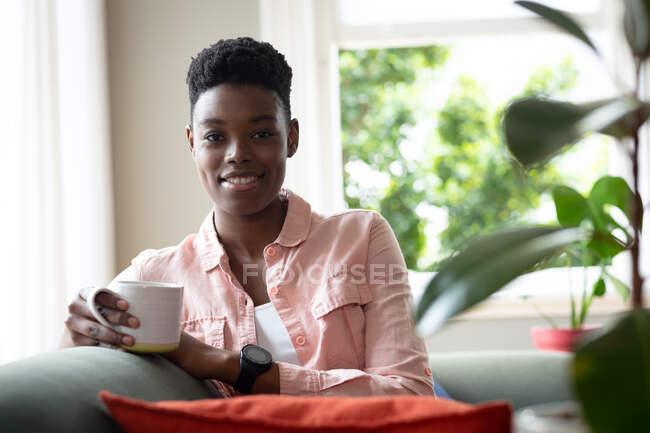 Портрет афро-американської жінки, яка сидить на дивані, п'є каву, дивлячись на камеру і посміхаючись. Перебуваючи вдома в ізоляції під час карантину.. — стокове фото