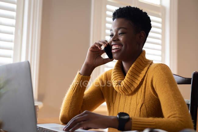 Африканская американка использует ноутбук, разговаривая на смартфоне на кухне. оставаться дома в изоляции во время карантинной изоляции. — стоковое фото