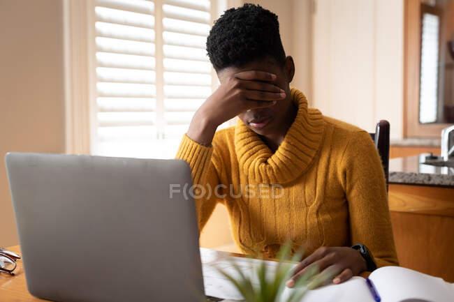 Mulher afro-americana usando laptop esfregando os olhos na cozinha. ficar em casa em auto-isolamento durante o confinamento de quarentena. — Fotografia de Stock