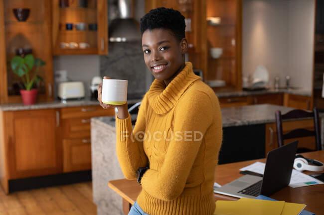 Африканская американка, стоящая на кухне и пьющая кофе, глядя в камеру и улыбаясь. оставаться дома в изоляции во время карантинной изоляции. — стоковое фото