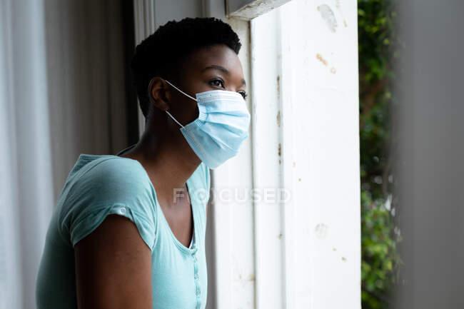 Портрет афро-американської жінки, одягненої в маску обличчя, дивлячись у вікно вдома. Залишатися вдома в ізоляції в карантині. — стокове фото