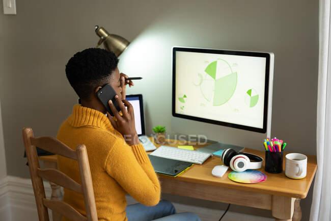 Mulher afro-americana falando no smartphone e usando o computador enquanto trabalhava em casa. ficar em casa em auto-isolamento em quarentena — Fotografia de Stock