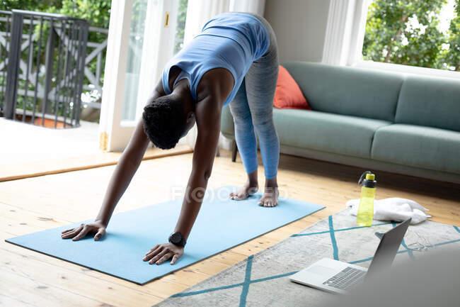 Afro-americana realizando exercícios de alongamento em casa. ficar em casa em auto-isolamento em quarentena — Fotografia de Stock