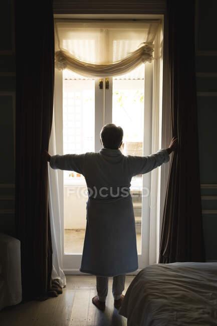 Uma mulher afro-americana sênior ao pé de uma janela numa sala de dormir. estilo de vida de aposentadoria em auto-isolamento durante coronavírus covid 19 pandemia. — Fotografia de Stock