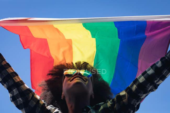 Змішана расова жінка стоїть на даху і тримає прапор веселки. Статева рідина lgbt ідентичність Расова рівність. — стокове фото
