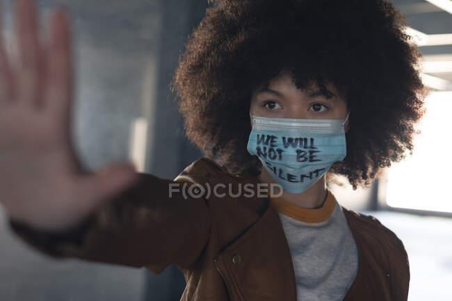 Змішана расова жінка носить маску обличчя з гаслом, що тримає її за руку. Статева рідина lgbt ідентичність Расова рівність. — стокове фото