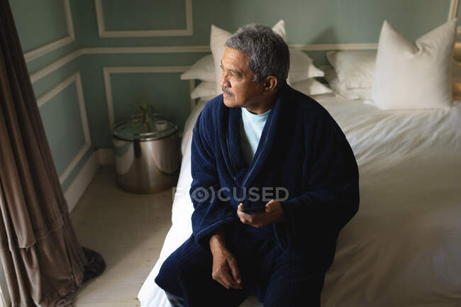 Senior african american man sitting on a bed using smartphone in a sleeping room. retirement lifestyle in self isolation during coronavirus covid 19 pandemic. — Stock Photo