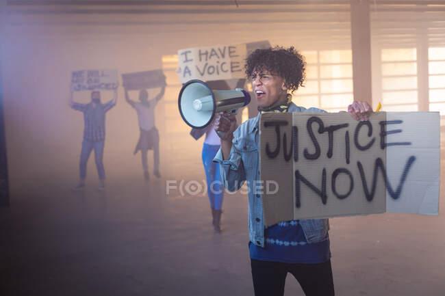 Змішана расова людина кричить у мегафоні, тримаючи знак протесту. протестуючих на задньому плані. Статева рідина lgbt ідентичність Расова рівність. — стокове фото