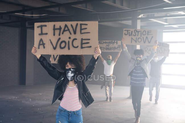 Багатоетнічна група людей у масках на обличчі тримає знак протесту. Статева рідина lgbt ідентичність Расова рівність. — стокове фото
