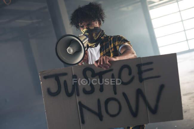Смешанный расист в маске, держащий знак протеста, кричащий в мегафоне. Концепция гендерного расового равенства. — стоковое фото