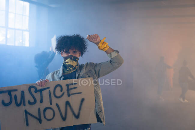 Mixed race man wearing face mask holding protest sign raising fist. with protesters in the background. gender fluid lgbt identity racial equality concept. — Stock Photo