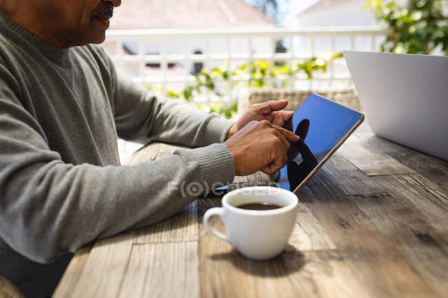 Homem americano africano sênior sentado no terraço usando tablet digital bebendo café. estilo de vida de aposentadoria em auto-isolamento durante coronavírus covid 19 pandemia. — Fotografia de Stock